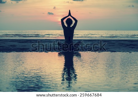 Yoga, silhouette young woman on the beach at sunset, harmony of health.
