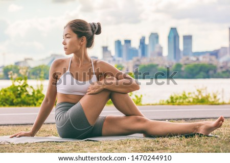 Photo of  Yoga stretch exercise fit Asian woman stretching lower back for spine health on city outdoor fitness class in park. Seated spinal twist.