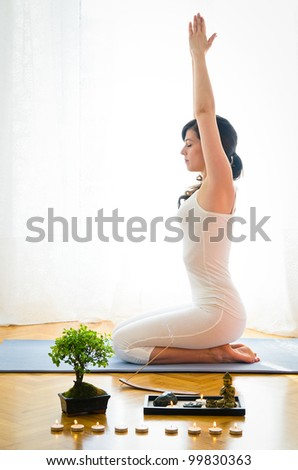 Yoga, stretching and meditation at home. Woman doing yoga pose with bonsai and candle indoor. Caucasian young model meditate.
