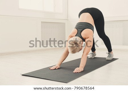 Yoga stretching. Woman in dog pose. Young slim girl makes exercise. Healthy lifestyle, fitness concept