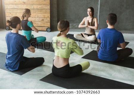 Yoga teacher and beginners in class, making asana exercises. Lotus pose. Healthy lifestyle in fitness club. Stretching with coach, back view