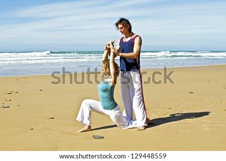 Yoga teacher teaches student yoga on the beach