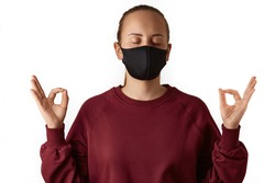 Yoga time. Young european woman wears face mask and burgundy sweatshirt, practices yoga, holds hands in mudra gesture, feels zen, nirvana, keeps eyes closed, isolated over white background