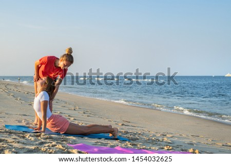 Yoga trainer. Yoga class instructor helps beginner to make asana exercises. Woman doing yoga with trainer on the beach