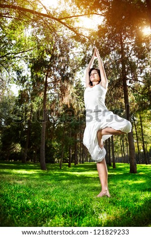 Yoga tree pose by woman in white costume on green grass in the park around pine trees