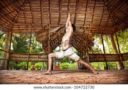 Yoga virabhadrasana I warrior pose by fit man in white trousers on the drought earth in yoga shala, Varkala, Kerala, India