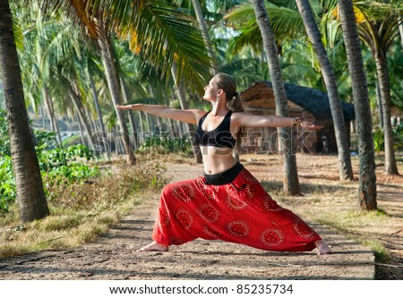 Yoga virabhadrasana II warrior pose by beautiful Caucasian woman in red Indian trousers with symbol om on the road in palm tree forest with house at background in India, Kerala, Varkala