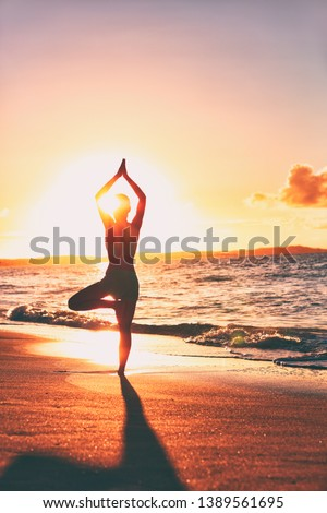 Yoga wellness retreat class on morning sunrise beach landscape. Silhouette of girl standing in tree pose meditation vertical background. #1389561695