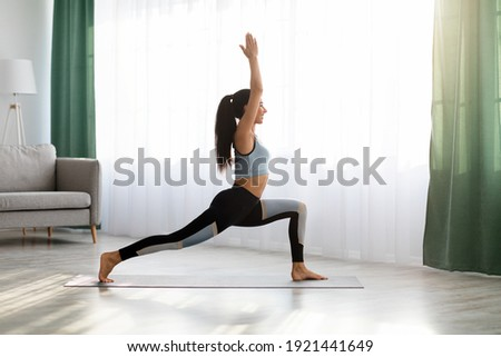 Yoga woman in sportswear exercising at home, standing in warrior pose on fitness mat, side view, copy space, full length shot. Healthy, sporty lifestyle, yoga practicing at home during self-isolation