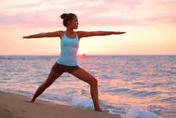 Yoga woman in zen meditating in warrior pose relaxing outside by beach at sunrise or sunset. Female yoga instructor working out training in serene ocean landscape. Big Island, Hawaii, USA.