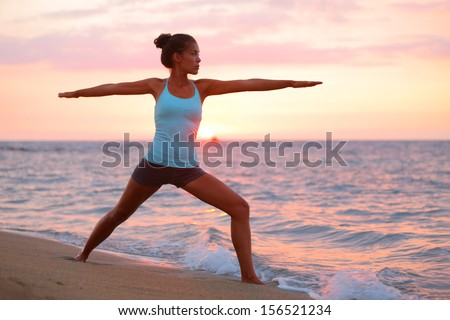 Stock Photo Yoga woman in zen meditating in warrior pose relaxing outside by beach at sunrise or sunset. Female yoga instructor working out training in serene ocean landscape. Big Island, Hawaii, USA.