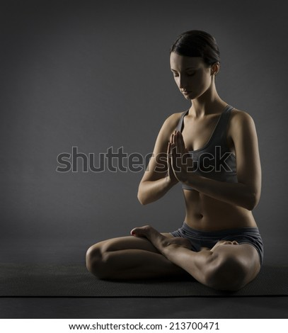 Yoga woman meditate sitting in lotus pose Silhouette of exercise girl over black background