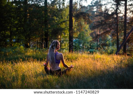 Yoga woman meditates in a clearing in the woods. Peaceful and harmony.