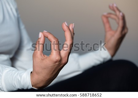 Yoga woman meditating and making a zen symbol with her hand - Shutterstock ID 588718652