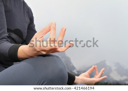 Yoga woman meditation on mountain peak, close up of hands - Shutterstock ID 421466194