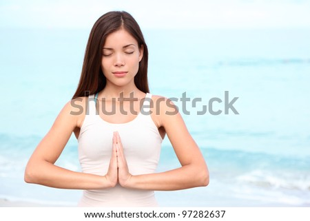 Yoga woman meditation. Young asian woman meditating doing yoga on beach. Beautiful serene mixed race Asian Chinese / Caucasian female fitness model relaxing on beach.