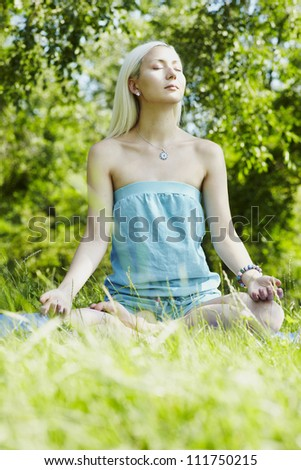 Yoga woman on green park. Meditation and relaxation