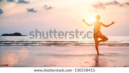 Yoga woman performs an exercise on the beach during sunset.