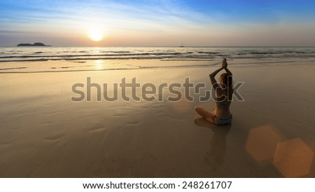 Yoga woman sitting in lotus pose on the beach during amazing sunset. Harmony.