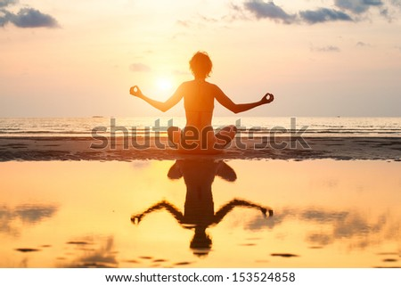 Yoga woman sitting in lotus pose on the beach during sunset, with reflection in water.