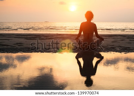 Yoga woman sitting in lotus pose on the beach during sunset, with reflection in water - in bright colors.