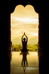 Yoga woman sitting in lotus pose on the temple during sunrise to reflection in floor, vintage style color effect
