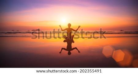 Yoga woman sitting on sea coast at sunset.