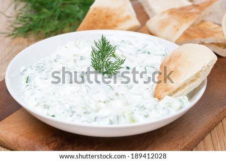 yoghurt sauce tzatziki with herbs, cucumber and garlic and pita bread, close-up, horizontal