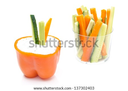 yoghurt sauce with herbs in half of orange pepper and assorted sliced �¢??�¢??fresh vegetables in a glass, isolated on a white background