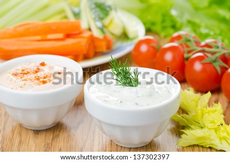yoghurt sauce with herbs, sauce with sun-dried tomatoes and paprika to assorted fresh vegetables on a wooden table horizontal close-up