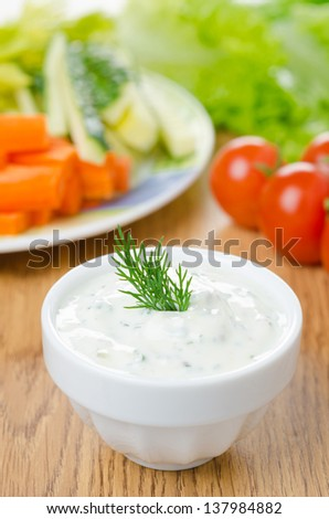 yoghurt sauce with herbs to assorted fresh vegetables on a wooden table