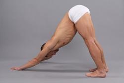 Yogi man do downward dog Adho Mukha Svanasana yoga standing pose grey background, asana.