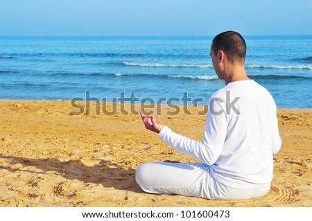 yogi man dressed in white meditating on the beach
