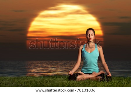 Yogi sunrise. A sportive beautiful woman training yoga on the beach at dawn.