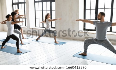 Yogi trainer and multi-ethnic young people standing in Warrior two position. Yoga class led by caucasian coach, deep hip-opening pose strengthens muscles of thighs and buttocks, mind and body activity