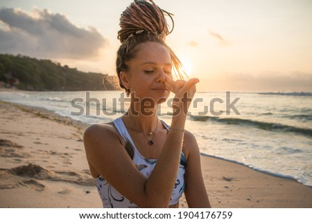 Yogi woman practicing Nadi Shodhana Pranayama, Alternate Nostril Breathing. Control prana, control of breath. Breathing exercise. Self care concept. Sunset time. Yoga retreat. Thomas beach, Bali