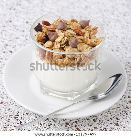 yogurt and granola with chocolate drops in a glass beaker closeup