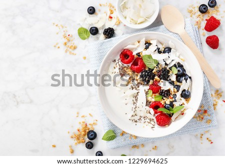 Yogurt bowl with fresh berries, granola and coconut chips served on white marble background. View from above with copy space. Horizontal.