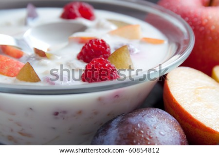 Yogurt. Glass bowl filled with yogurt mixed with fruit pieces arranged with spoon and some fruits around