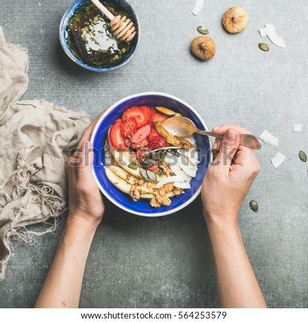 Yogurt, granola, seeds, fresh and dry fruit and honey in blue ceramic bowl in woman' s hands over grey concrete background, top view, square crop. Clean eating, detox, dieting, vegetarian food concept #564253579