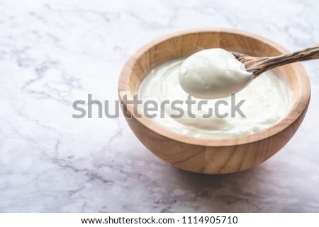 Yogurt in wooden bowl on marble table #1114905710
