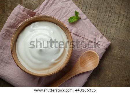Yogurt in wooden bowl on wooden background with pink cotton and wooden spoon. plain yoghurt. yogurt. yoghurt.