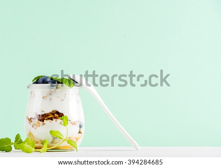 Yogurt oat granola with jam, blueberries and green leaves in glass jar on mint pastel backdrop, copy space