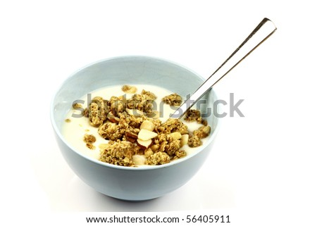 yogurt with crunchy breakfast cereals with all sorts of nuts in a blue bowl with a spoon