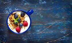 Yogurt with granola and fresh berries on an old wooden board with copy space for text.