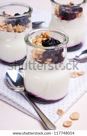 yogurt with muesli and berries in glass jars