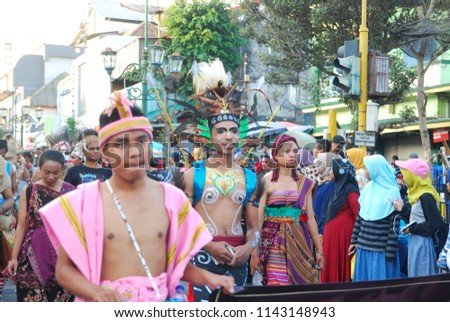 YOGYAKARTA, INDONESIA - JULY 2018: a group of people wearing masks and traditional clothing is marching on malioboro street yogyakarta in the opening ceremony of yogyakarta art festival (FKY) 30 #1143148943