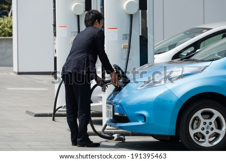 YOKOHAMA, JAPAN - APRIL 24, 2014: A businessman plugs in an electric car Nissan Leaf to charge the car at a charging station in front of the entrance of Nissan\'s Global Headquarters.