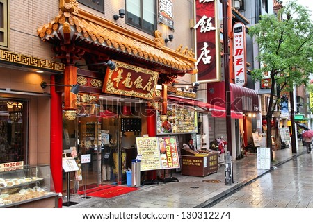YOKOHAMA, JAPAN - MAY 10: People walk past Chinese restaurant in Chinatown on May 10, 2012 in Yokohama, Japan. Yokohama's Chinatown is the largest in Japan and a popular tourism attraction. - stock photo