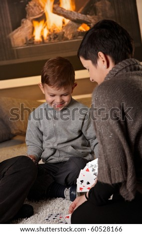 YoMother and 4 years old kid playing card game at home in a cold winter day.
